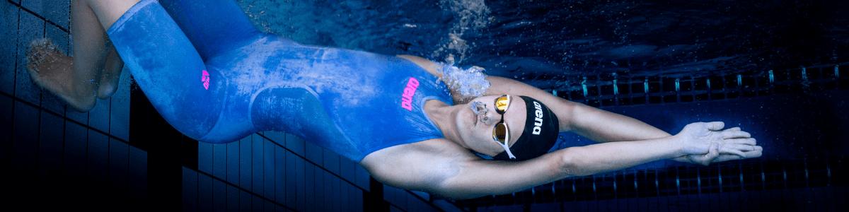nuotatrice in costume Arena Revo One occhialini e cuffia si spinge per nuoto in piscina
